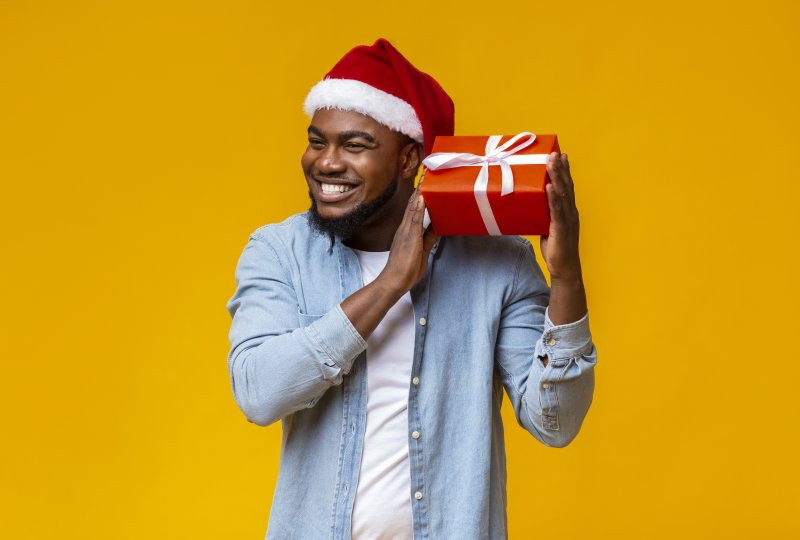 a man wearing a Santa hat and holding a present while smiling